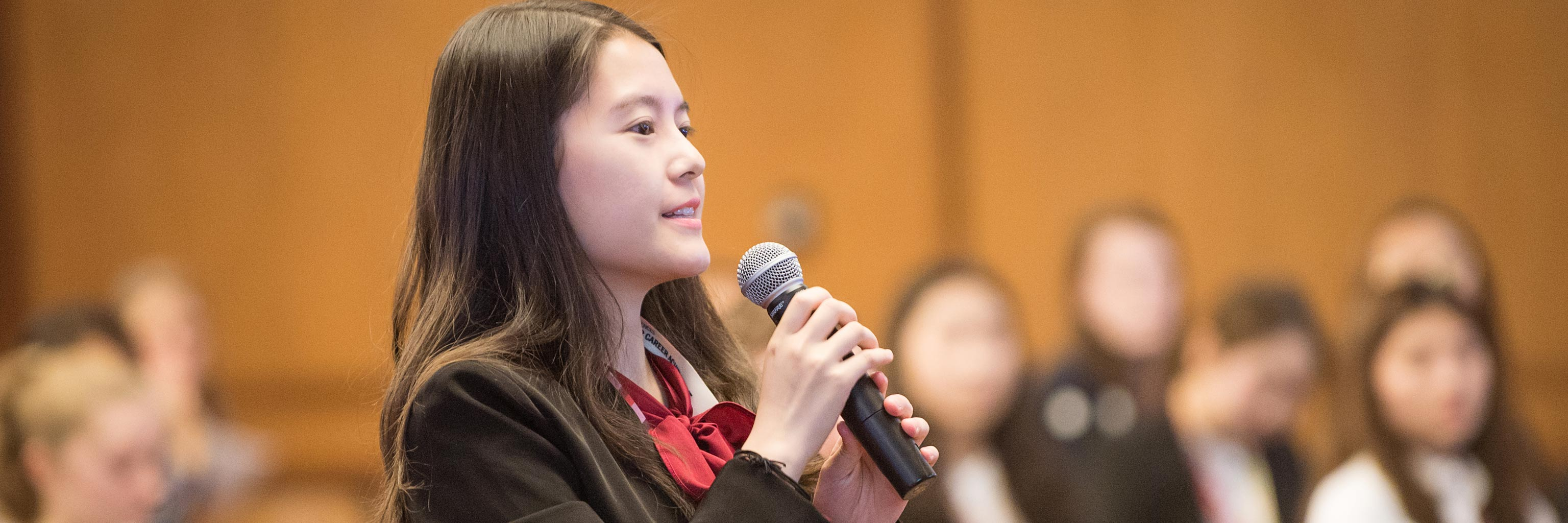Young Asian woman holds a mic up to speak.