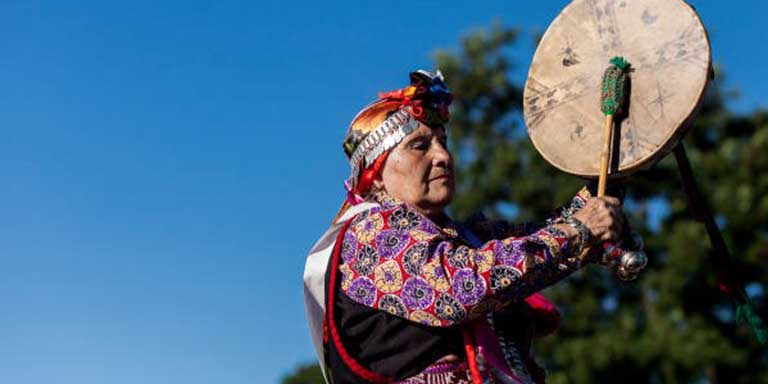 Native American person hitting drum with drum stick