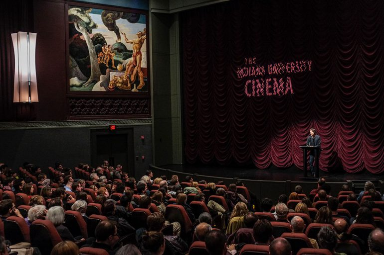 A full house at the IU Cinema watches as a man speaks from a podium on stage
